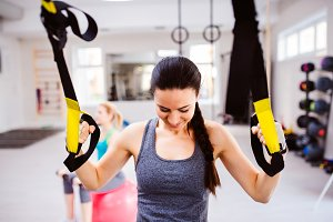 Woman in gym training arms with trx fitness strips