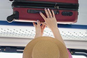 Young woman traveler in hat puts the suitcase on the top shelf in the train