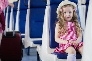 Portrait of little girl in panama hat sitting on armchair in the train looking at camera