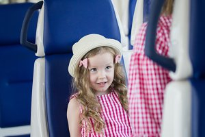 Cute little daughter sitting in front of her mom in train