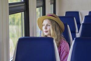 Young beautiful woman sitting near the window in speed train