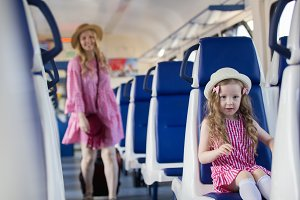 Happy young mother goes with suitcase to her little daughter who sitting on armchair in train