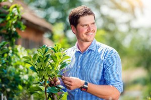 Handsome gardener with little tree, green sunny nature