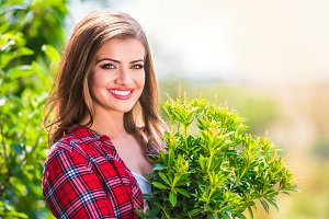 Beautiful gardener with little tree, green sunny nature