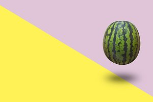Watermelon isolated on a yellow and pink pastel background with a shadow