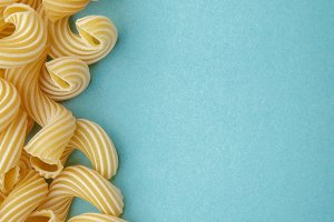Pasta penne rigate on blue background