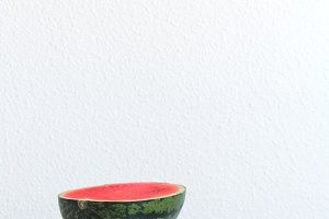 Half of watermelon on a white table with copy space. Vertical