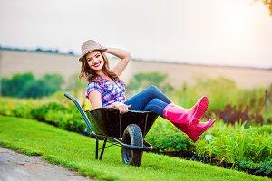 Woman sitting in wheelbarrow in sunny green garden