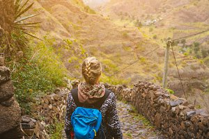 Female hiker with blue backpack staying on the stony cobbled trekking trail leading down to the valley between barren mountain peak on Santo Antao island, Cabo Verde