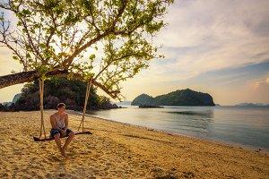 Young boy enjoys sunset n Ko Hong island in Thailand
