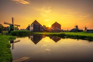 Sunset above farm houses and windmills of Zaanse Schans in the Netherlands