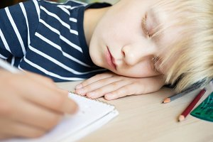 Boy sleeping while doing his homework in notebook.