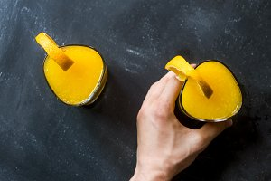 hand holding and grabbing the orange fruit smoothie from the dark chalkboard