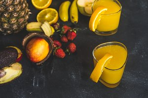 close up two glasses with orange juice near fresh fruit mix