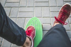 close up man's legs in sneakers sitting on the bench with skateboard