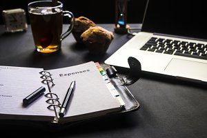 close up dark table background with opened notebook diary and sweet food