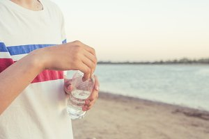 close up person holding bottle of pure cold water on the summer beach
