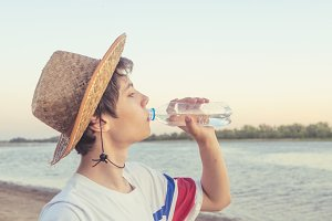 portrait of young man in summer hat on the tropical beach drinking water