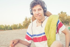 young man on the summer beach in headphones vintage toned