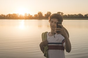 portrait of young teenage boy making a selfie with his smartphone on the beach during sunset