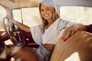 Cheerful woman driving a vintage car