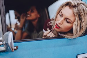 Women on road trip doing makeup