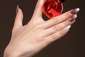 Beautiful classic manicure on female hand with oil for cuticles . Close-up.