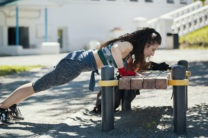 Young brunette woman doing pushups from the bench at sunny day outdoors