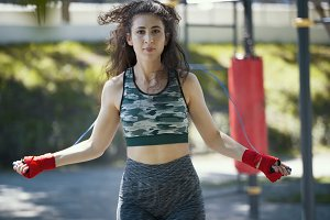 Portrait of caucasian young woman with long curly hair workout in the park at sunny day