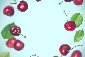 Frame of flying berries of a cherry on a blue background