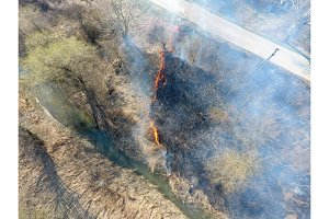 Burning dry grass along the irrigation canal. Smoke and the flame of dry grass. Burnt dry grass.