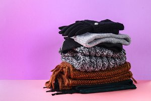 Winter and autumn clothes, hats, scarves, gloves on a purple pastel background.