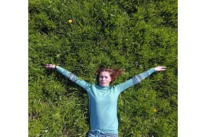 The girl lies in a turquoise dress on the lawn. beautiful girl lying down of grass