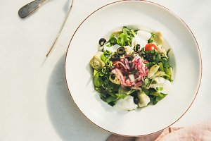 Fresh green summer salad with artichokes, top view