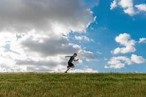 Boy Running Across Grassy Hill