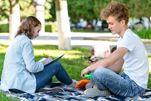 The guy with the girl. Pupils in summer in nature. After the institute they rest in the park. Writes the abstract. In the hands of a smartphone communicates in social networks.