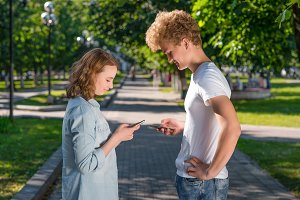 The boy and girl are facing each other. Summer in nature. In his hands holds a smartphone. Writes the phone number. Emotion dating in the park. The concept of dating in nature.