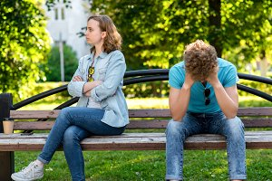 The guy and girl quarreled outside. Summer in the park on a bench. The problem is in the relationship. Misunderstanding in conversation. Conflict parting.