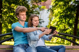 Young boy and girl. Students in summer in a park nature. After school they sit on a bench. In hands of keeps te tablet watching video on social networks. Smiling happy showing thumbs on screen.