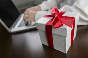 Computer by Gift Box in Red Ribbon