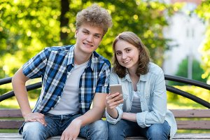 Young couple girl boy. Summer in park on a bench. In his hands holds a smartphone. Happy smiling close-up. Emotions of happiness and pleasure. The student rests after school.