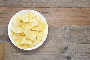 Potato chips in bowl on wooden table