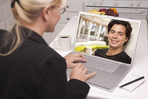 Young Woman In Kitchen Using Laptop