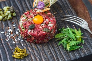 Steak tartare served with capers, pickled cucumbers and chopped onion.