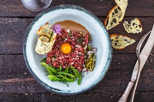 Delicious steak tartare with yolk, capers, green onion and bread