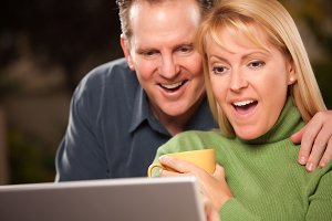 Excited Couple Using Their Laptop