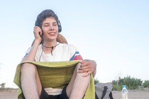 young happy boy in casual outfit with towel sitting on the beach listening to music copy space