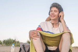 young hipster chilling on the beach sand on a summer day listen music with headphones