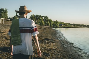 back view of young man in summer hat walking on the beach during golden hour