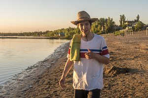young smiling happy teenage boy in summer hat with towel on the sea coast beach during golden hour